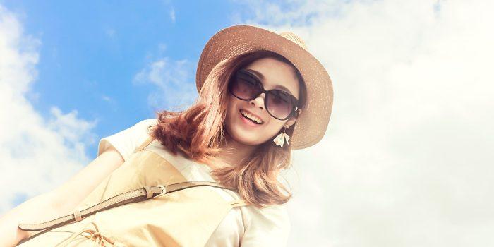 femeie care poarta palarie si ochelari de soare