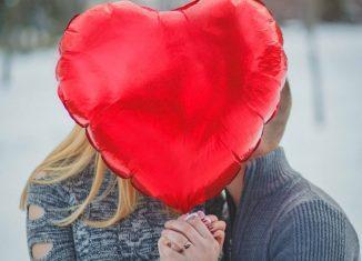 femeie si barbat care tin un balon rosu sub forma de inima