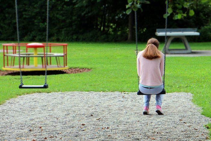 femeie care se da intr-un leagan de copii in parc