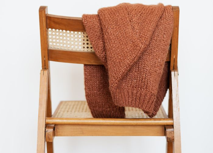 Pulover din lână așezat pe spătarul unui scaun, care se numărăr printre cele mai uzuale haine de iarnă