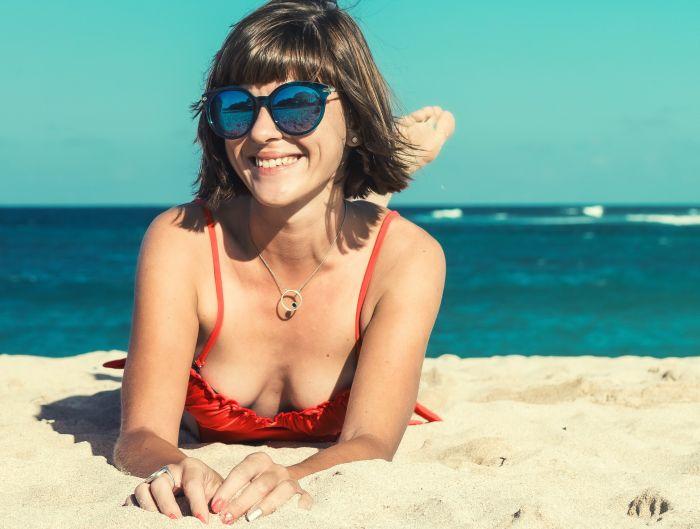 femeie care sta intinsa pe plaja la soare si poarta ochelari de soare