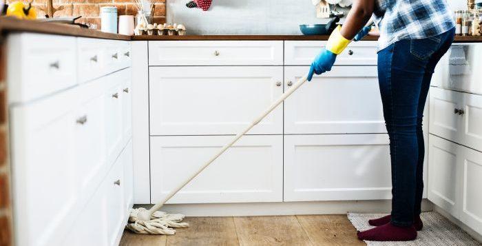 femeie care spala pe jos in bucatarie cu mopul