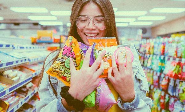 femeie la supermarket cu produse in brate
