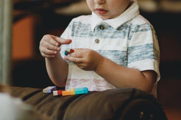 copil care se joaca cu cuburi