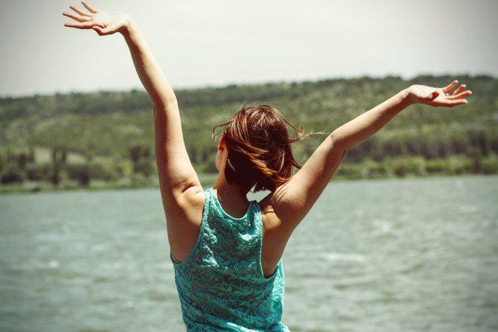 femeie fericita care sta cu fata la un lac