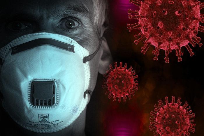 Barbat de varsta mijlocie care se protejeaza de coronavirus purtand o masca de protectie la gura