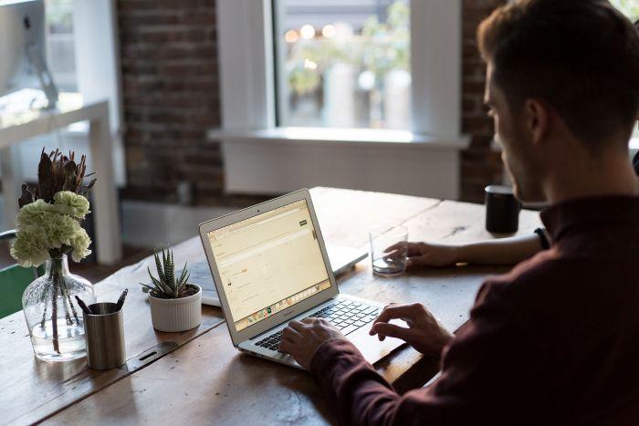 Bărbat care lucrează la laptop în camera birou de acasă